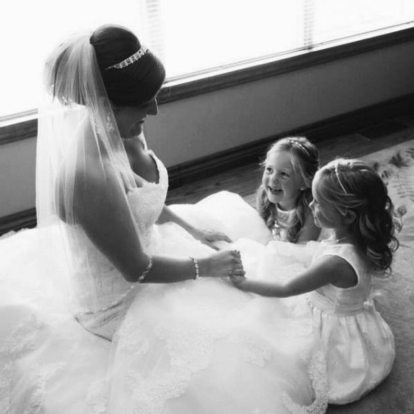 bride holding hands of little girls